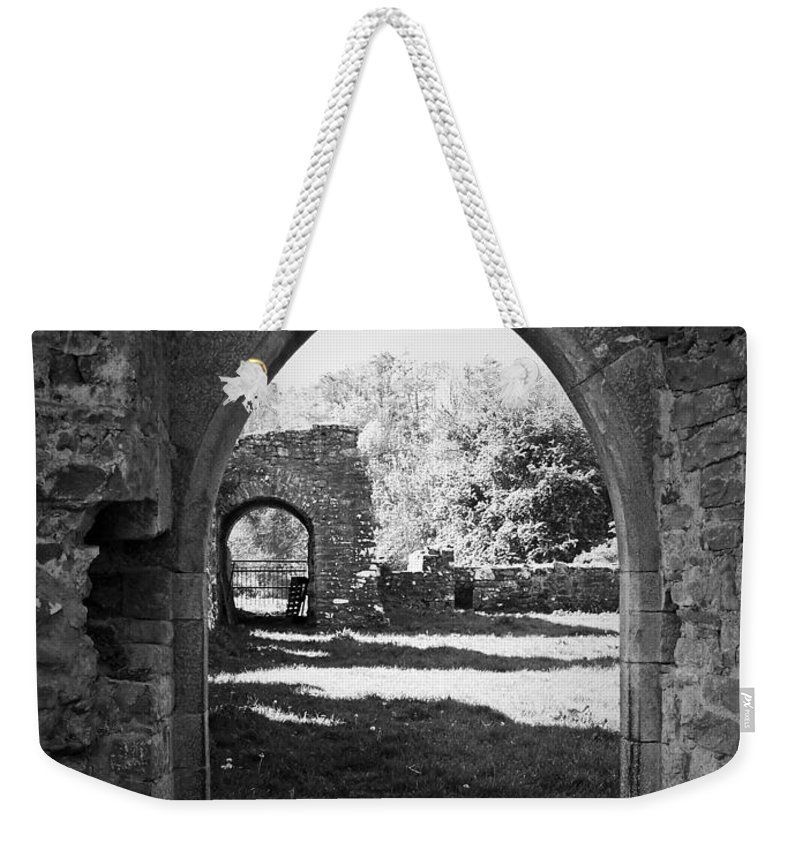 Irish Weekender Tote Bag featuring the photograph Arched Door At Ballybeg Priory In Buttevant Ireland by Teresa Mucha