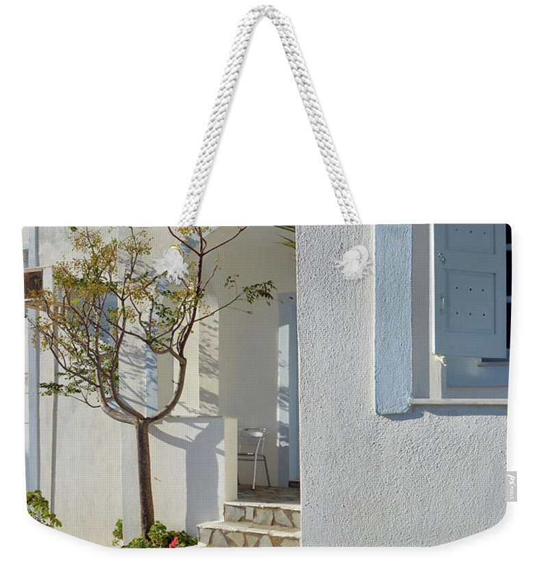 White Weekender Tote Bag featuring the photograph Beautiful White Mediterranean Architecture With Blue Frames. by Oana Unciuleanu