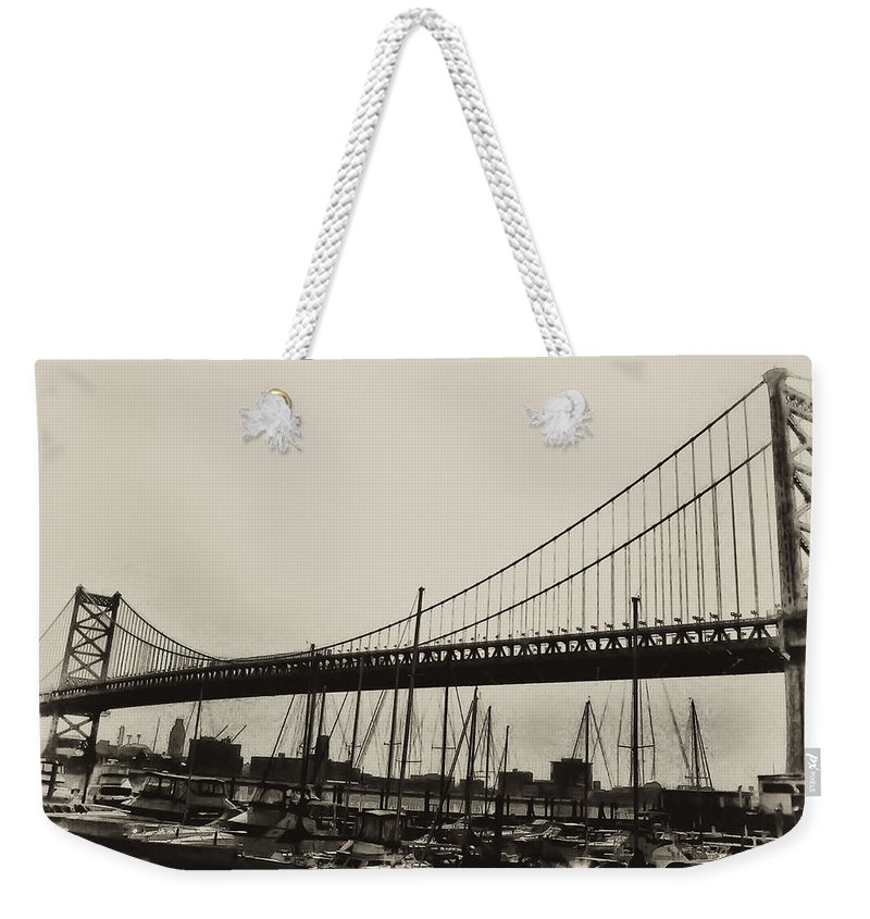 Philadelphia Weekender Tote Bag featuring the photograph Ben Franklin Bridge From The Marina In Black And White. by Bill Cannon