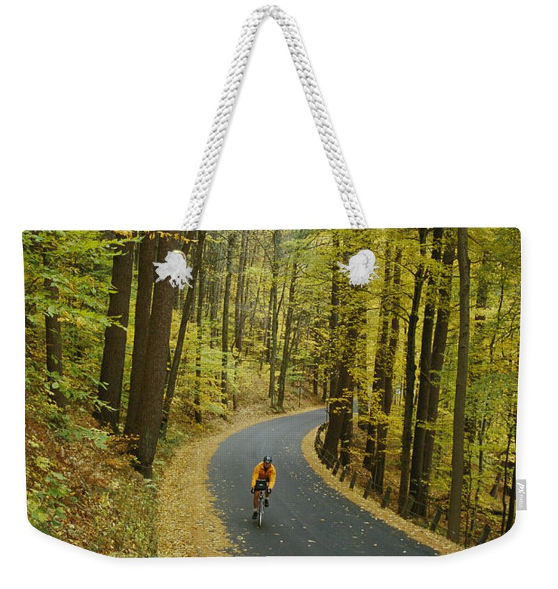 North America Weekender Tote Bag featuring the photograph Biker On Road Amidst Fall Foliage by Skip Brown