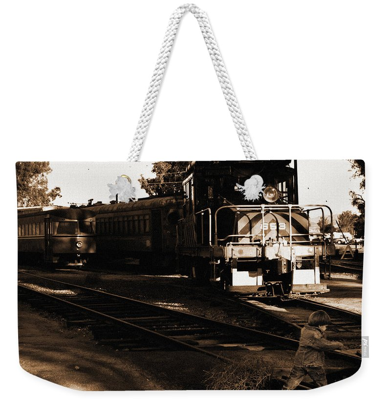 Train Weekender Tote Bag featuring the photograph Boy On The Tracks by Anthony Jones