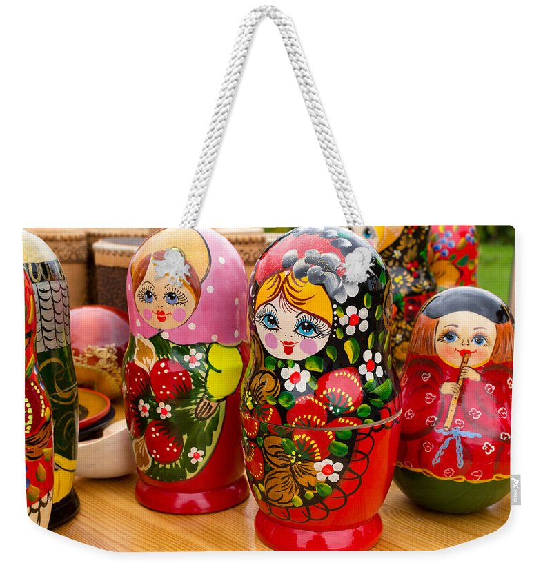 Russia Weekender Tote Bag featuring the photograph Bright Russian Matrushka Puzzle Dolls by John Williams