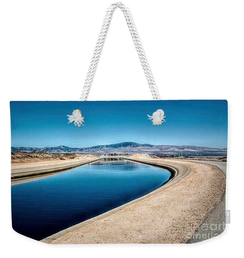 Against The Back Drop Of The Tehachapi Mountains And Wind Turbines. Weekender Tote Bag featuring the photograph California Aqueduct At Fairmont by Joe Lach