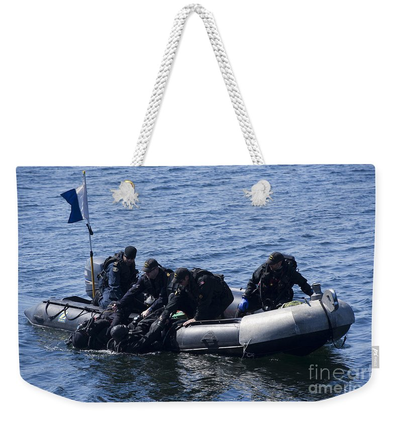 Canada Weekender Tote Bag featuring the photograph Canadian Divers Being Helped Aboard by Stocktrek Images