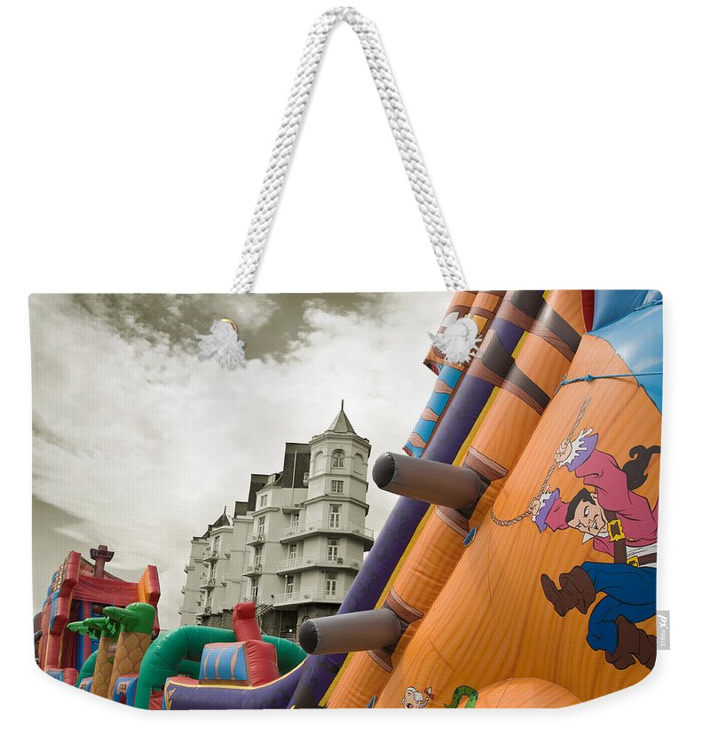 Childrens Weekender Tote Bag featuring the photograph Childrens Play Areas Contrast With The Victorian Elegance Of The Grand Hotel In Llandudno Wales Uk by Mal Bray