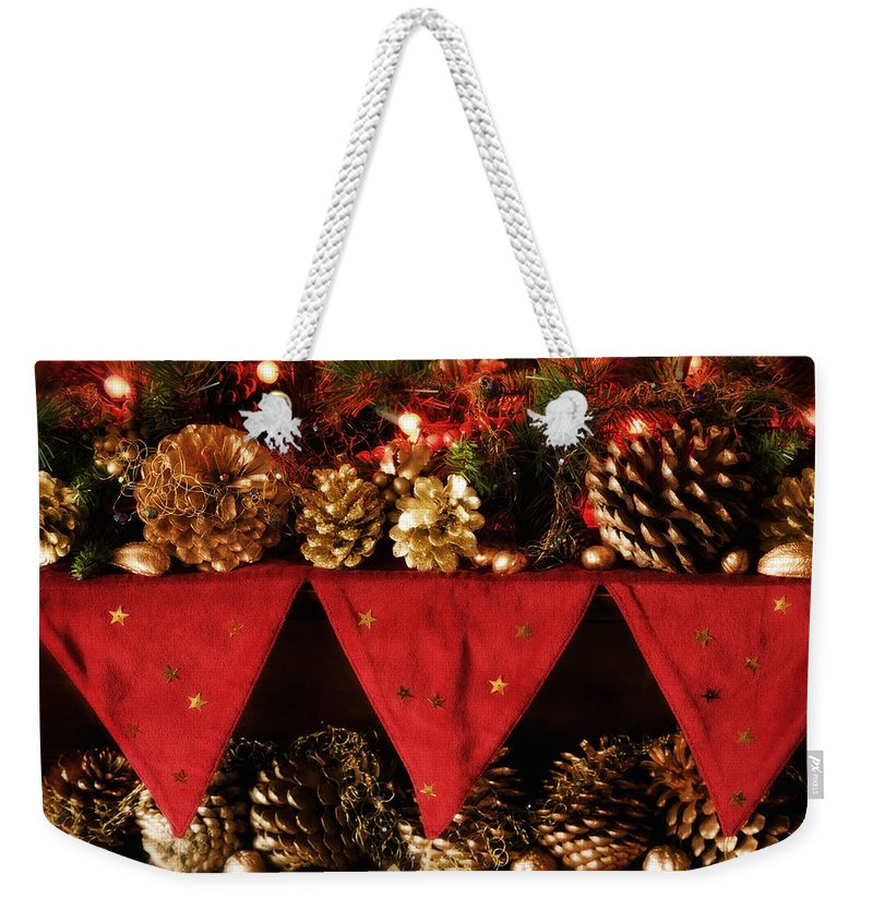 Christmas Weekender Tote Bag featuring the photograph Christmas Decorations Of Garlands And Pine Cones by Mal Bray