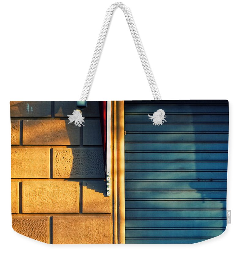 Sunset Weekender Tote Bag featuring the photograph Closed Shop Door At Sunset by Silvia Ganora