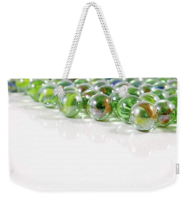 Marbles Weekender Tote Bag featuring the photograph Composition With Green Marbles On White Background by Daniel Ghioldi