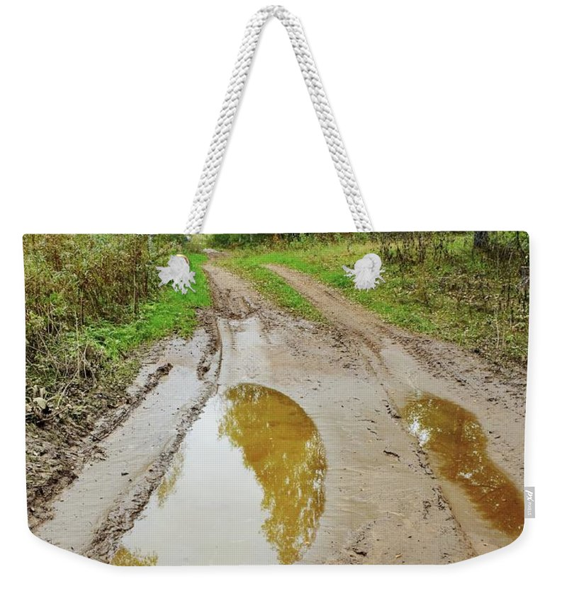 Attractive Weekender Tote Bag featuring the photograph Dirty Autumn Road With Brown Pools After Rain by Vadzim Kandratsenkau