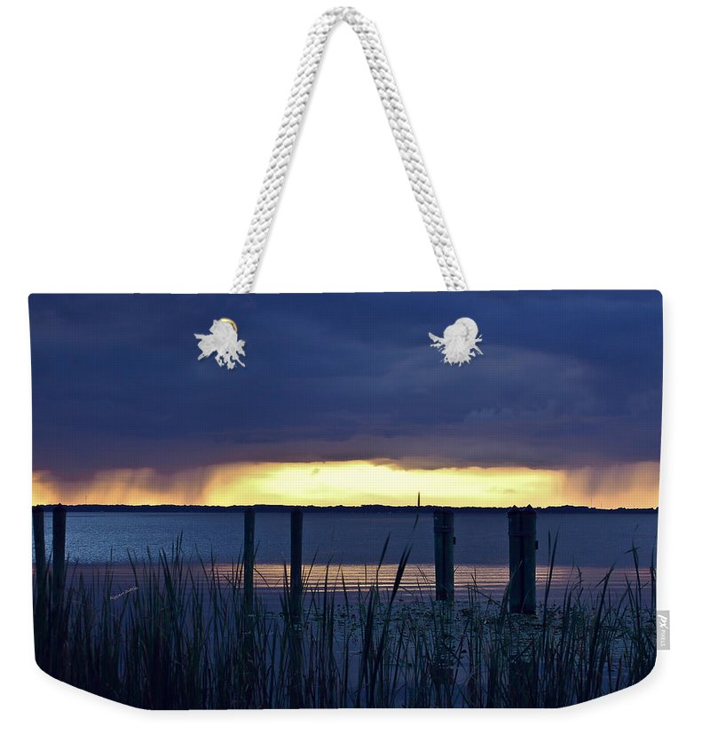 Lake Weekender Tote Bag featuring the digital art Distant Storms At Sunset by DigiArt Diaries by Vicky B Fuller