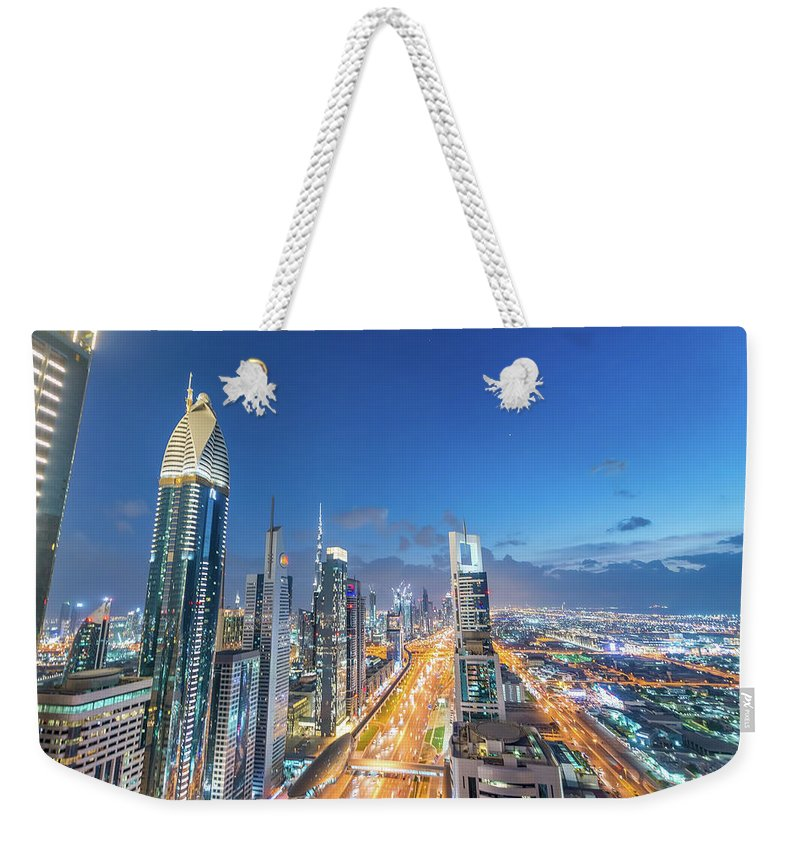 Dubai Weekender Tote Bag featuring the photograph Dubai Skyline Over Sheikh Zayed Road At Night by Giovanni Gagliardi