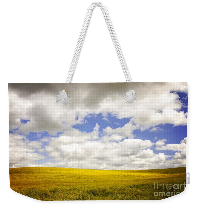 Yellow Weekender Tote Bag featuring the photograph Field With Dramatic Sky. by Sophie McAulay