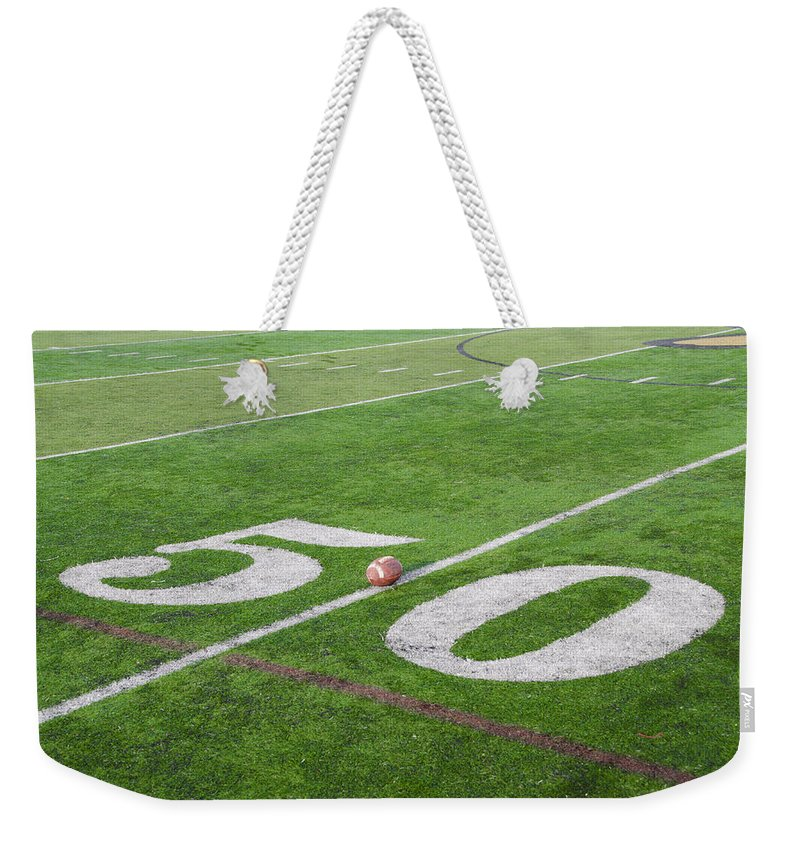 Football Weekender Tote Bag featuring the photograph Football On The 50 Yard Line by Bill Cannon