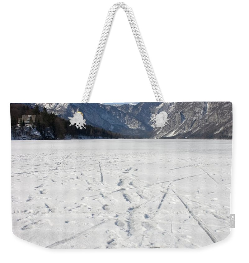 Footprints Weekender Tote Bag featuring the photograph Footprints On A Frozen Lake by Ian Middleton