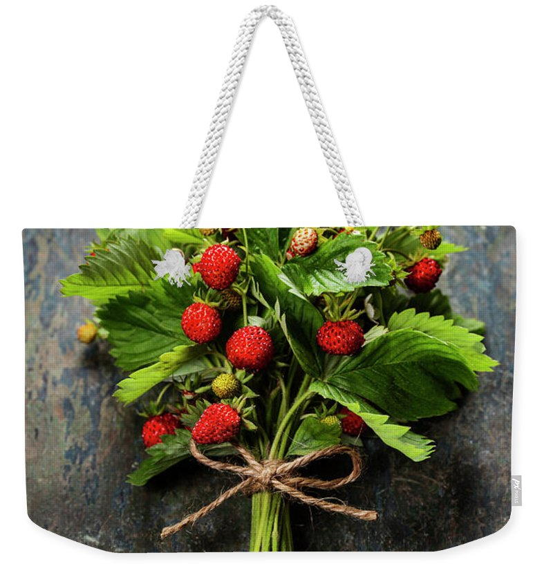 Wild Weekender Tote Bag featuring the photograph fresh Wild strawberries on wooden background by Natalia Klenova