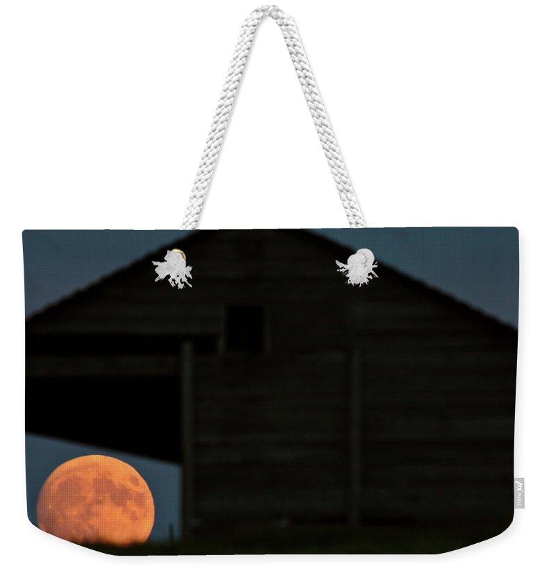 Building Weekender Tote Bag featuring the digital art Full Moon Seen Through Old Building Window by Mark Duffy