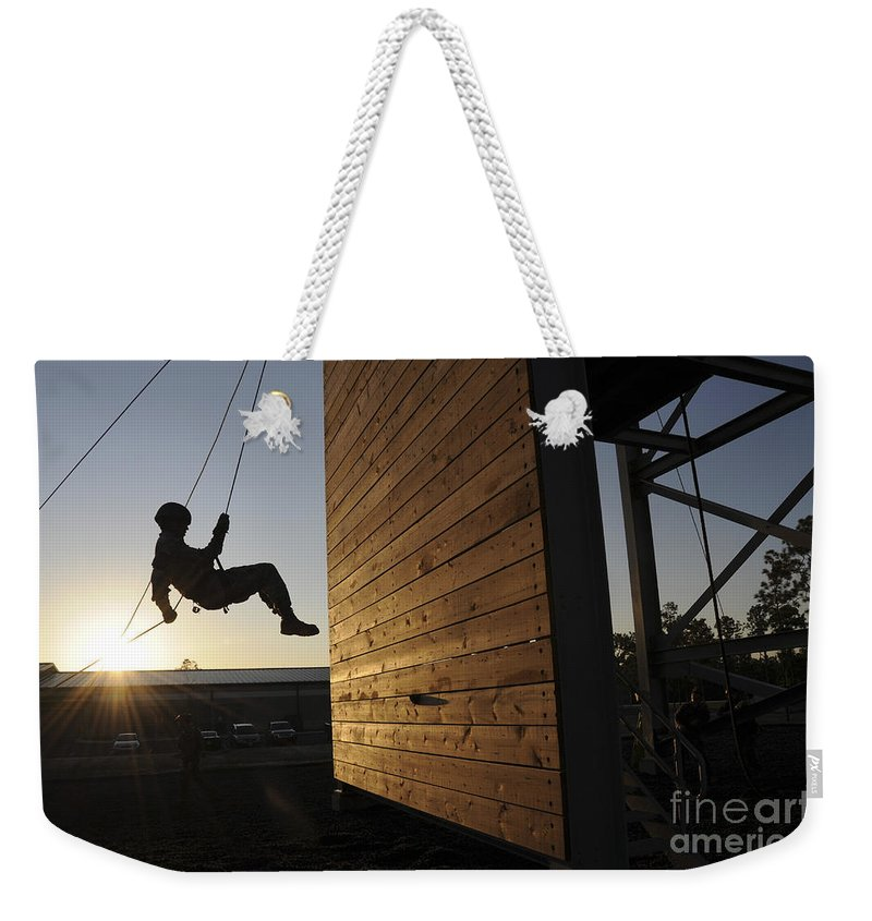 Soldier Weekender Tote Bag featuring the photograph Green Beret Rappels Down A 50 Foot Wall by Stocktrek Images