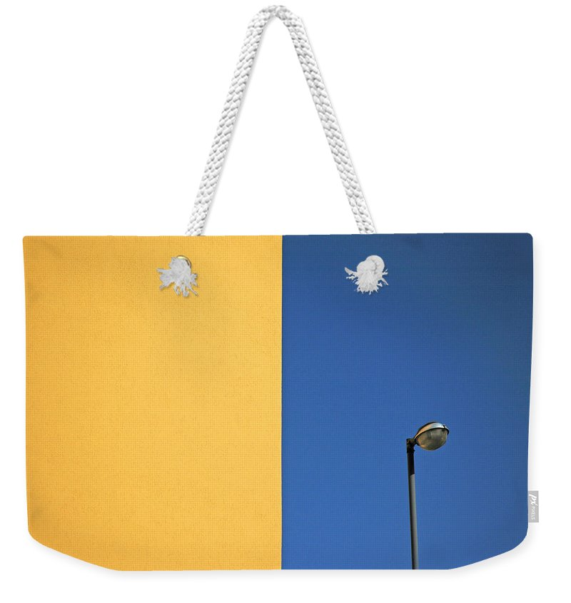 Urban Weekender Tote Bag featuring the photograph Half Yellow Half Blue by Silvia Ganora