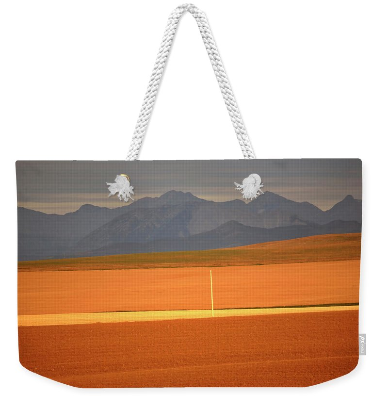Sunlit Weekender Tote Bag featuring the digital art High Plains Of Alberta With Rocky Mountains In Distance by Mark Duffy