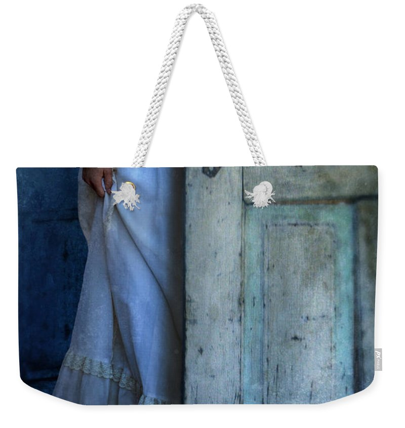 Woman Weekender Tote Bag featuring the photograph Lady In Vintage Clothing Hiding Behind Old Door by Jill Battaglia