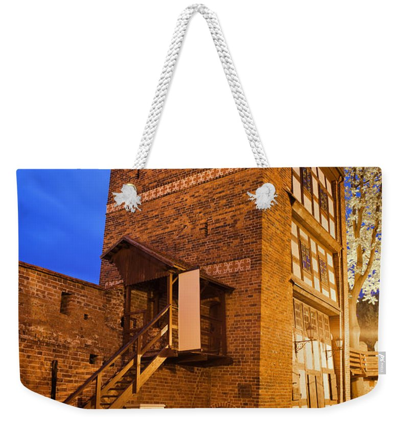 Leaning Weekender Tote Bag featuring the photograph Leaning Tower By Night In Torun by Artur Bogacki