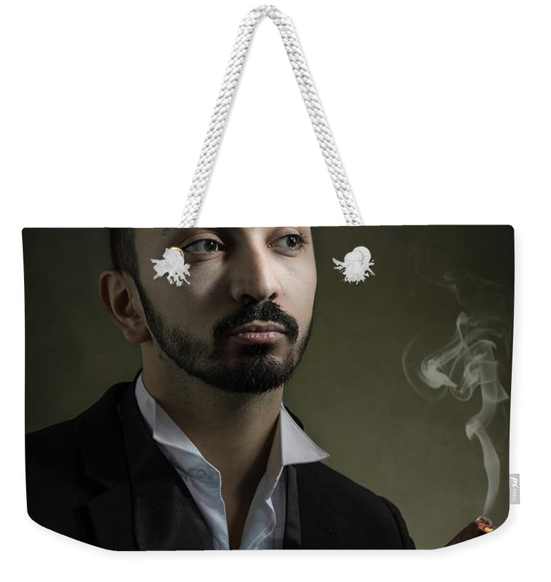 Portrait Weekender Tote Bag featuring the photograph Man Smoking A Cigar by Amanda Elwell