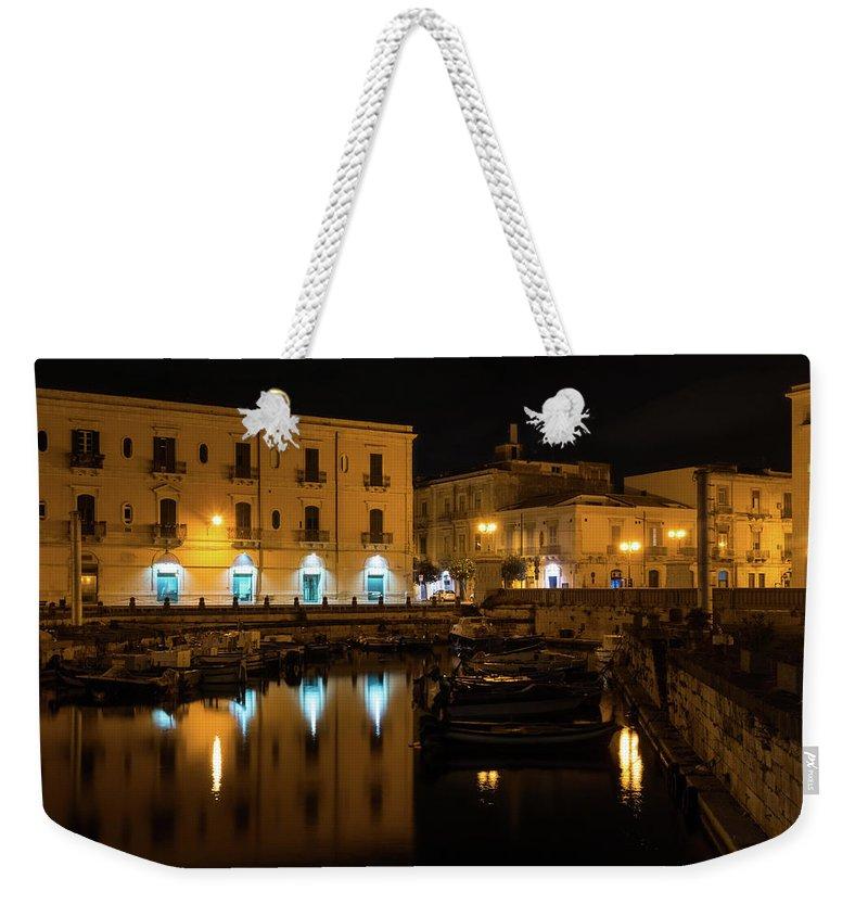 Georgia Mizuleva Weekender Tote Bag featuring the photograph Midnight Silence And Solitude - Syracuse Sicily Illuminated Waterfront by Georgia Mizuleva