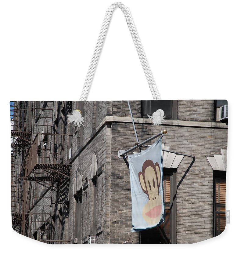 Street Scene Weekender Tote Bag featuring the photograph Monkey Flag by Rob Hans