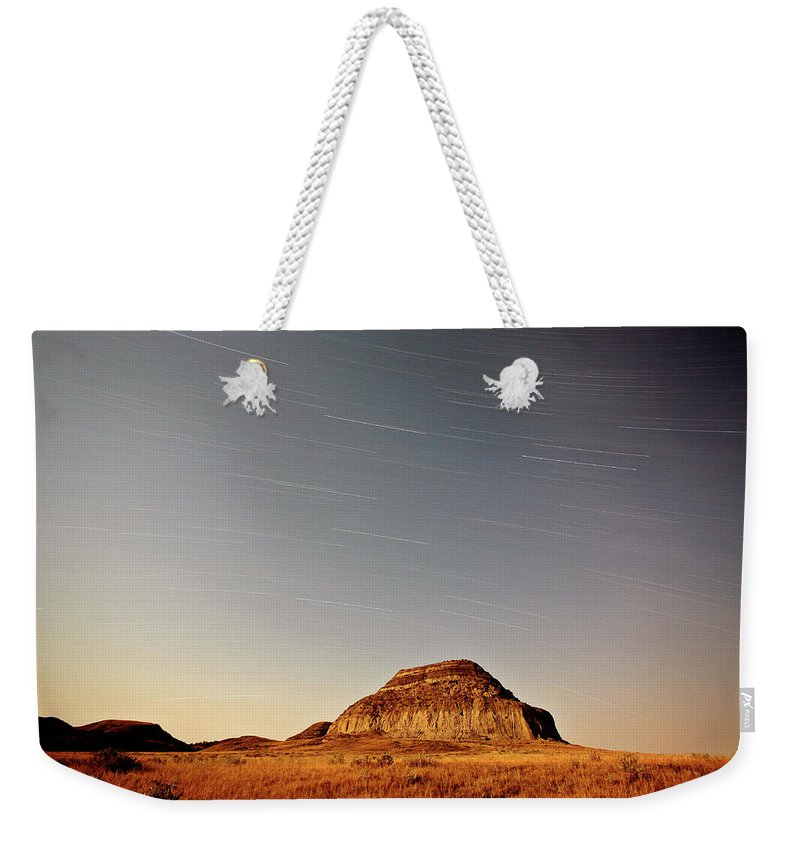 Castle Butte Weekender Tote Bag featuring the digital art Moon Lit Castle Butte And Star Tracks In Scenic Saskatchewan by Mark Duffy