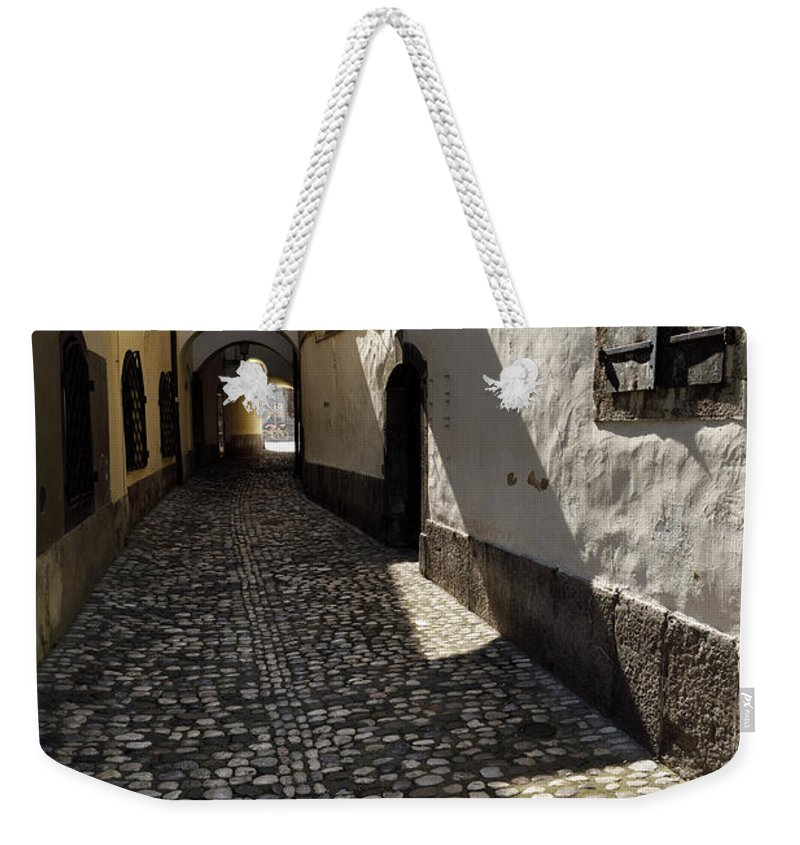 Narrow Weekender Tote Bag featuring the photograph Narrow Cobblestone Alley Ribji Trg Or Fish Square From Cankar Qu by Reimar Gaertner