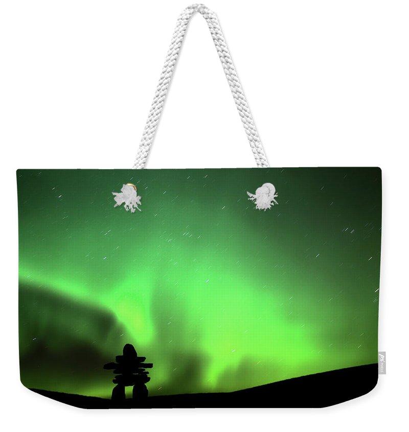 Inukchuk Weekender Tote Bag featuring the digital art Northern Light Above An Inukchuk In Saskatchewan by Mark Duffy