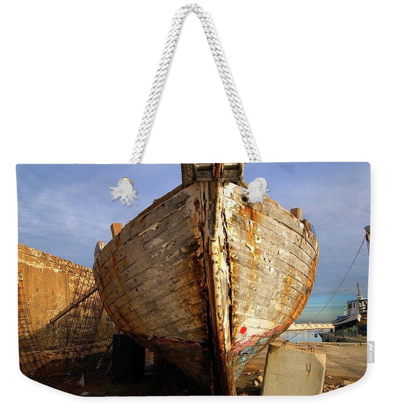 Old Weekender Tote Bag featuring the photograph Old Dilapidated Wooden Boat by Ofer Zilberstein