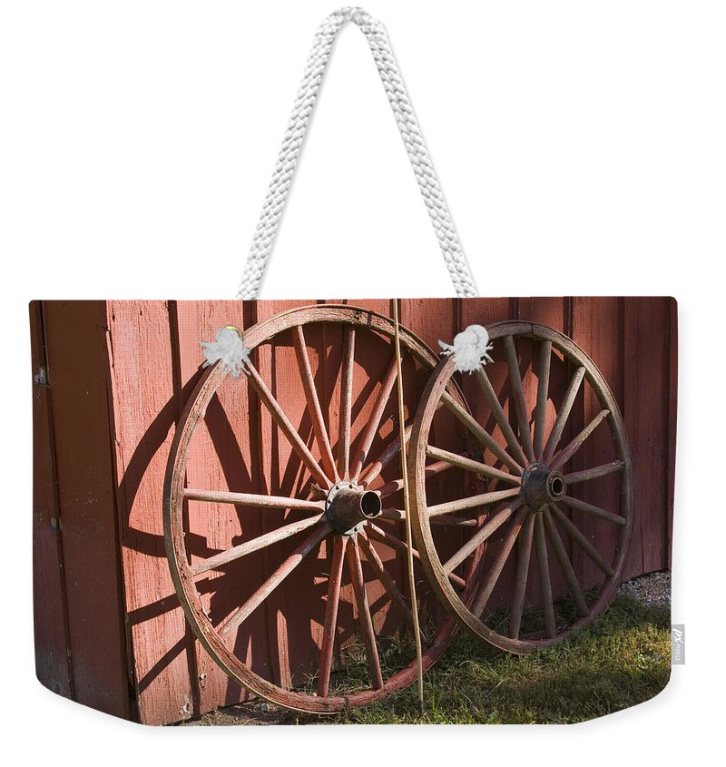 Old Time Antique Wagon Wheel Wood Wooden Red Barn Rural Country Farm Farming Round Weekender Tote Bag featuring the photograph Old Wagon Wheels by Andrei Shliakhau