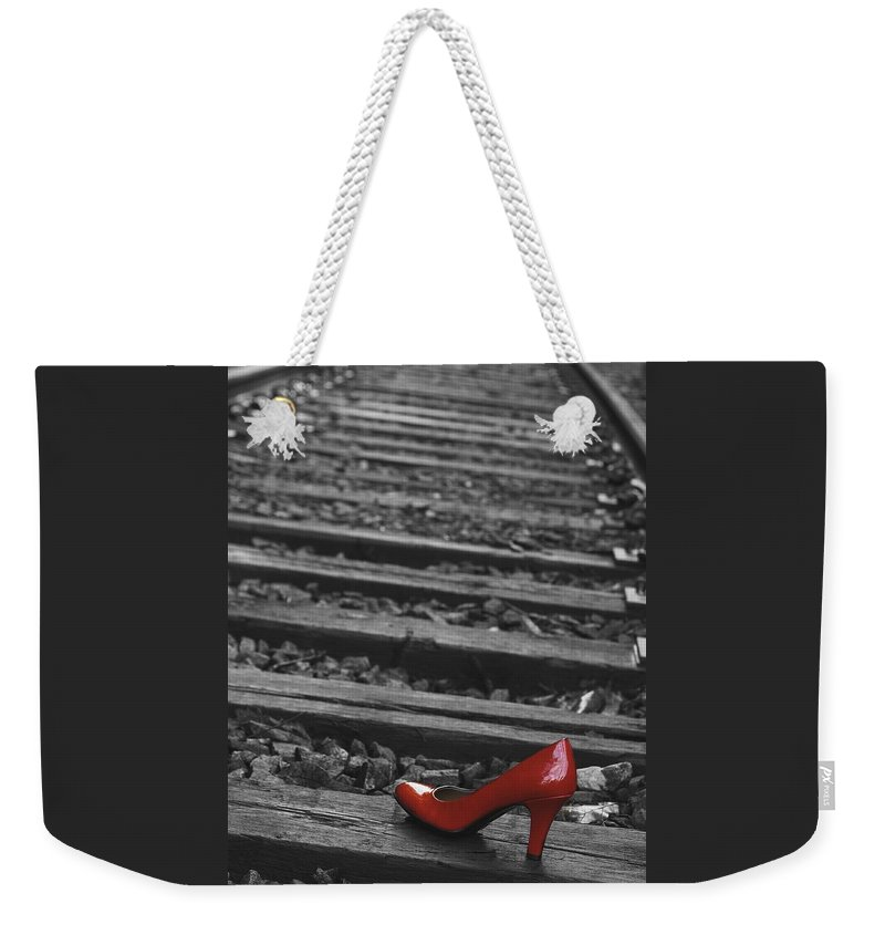 Red Woman's Shoe Weekender Tote Bag featuring the photograph One Red Shoe by Patrice Zinck