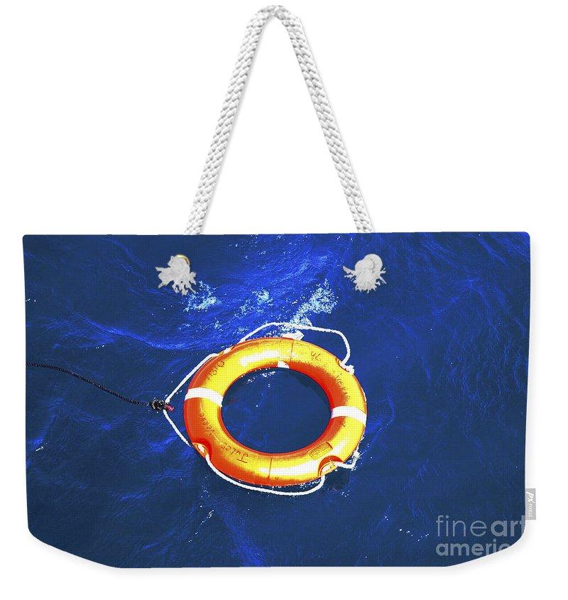 Orange Weekender Tote Bag featuring the photograph Orange Life Buoy In Blue Water by Jacki Costi