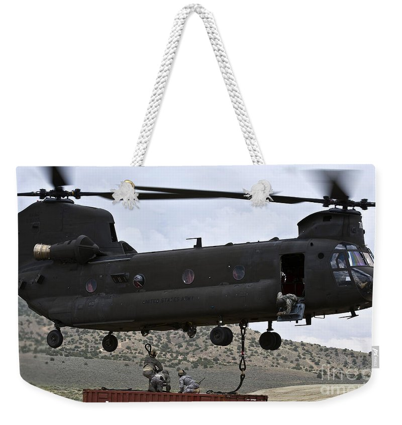 Nellis Air Force Base Weekender Tote Bag featuring the photograph Personnel Attach A Storage Container by Stocktrek Images