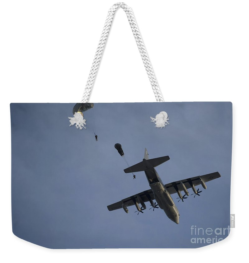 Exercise Emerald Warrior Weekender Tote Bag featuring the photograph Personnel Jump From A C-130 Hercules by Stocktrek Images