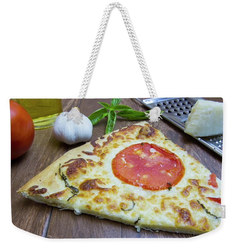 Baked Weekender Tote Bag featuring the photograph Piece Of Margarita Pizza With Ingredients by Karen Foley