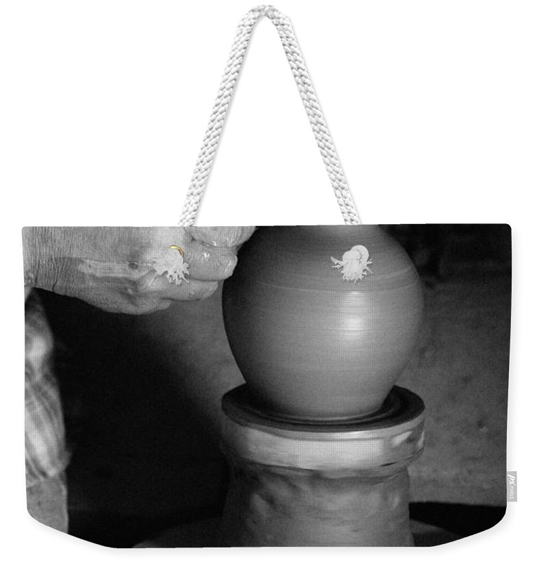 Azores Weekender Tote Bag featuring the photograph Potter At Work by Gaspar Avila