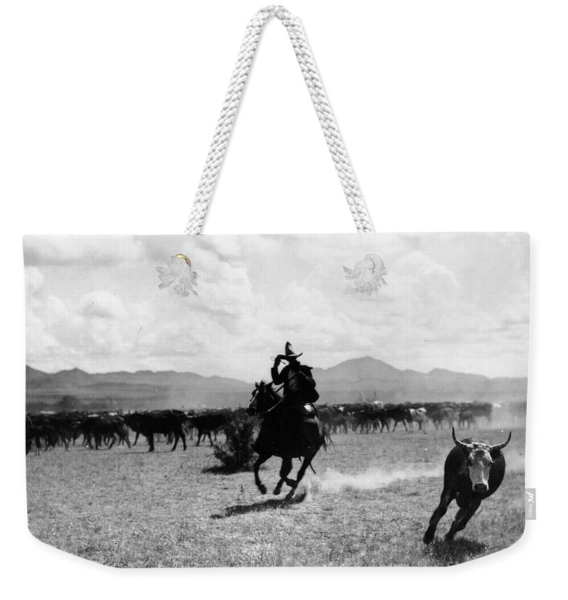 Raguero Cutting Out A Cow From The Herd (b/w Photo)wild West; Stetson; Cattle; Gallop; Round-up; Cowboy; Herding; Cattle; Plains; Old West; Western; Horse; Horseback; Rider; Riding; American Landscape; Atmospheric; Rustler Weekender Tote Bag featuring the photograph Raguero Cutting Out A Cow From The Herd by Raguero cutting out a cow from the herd