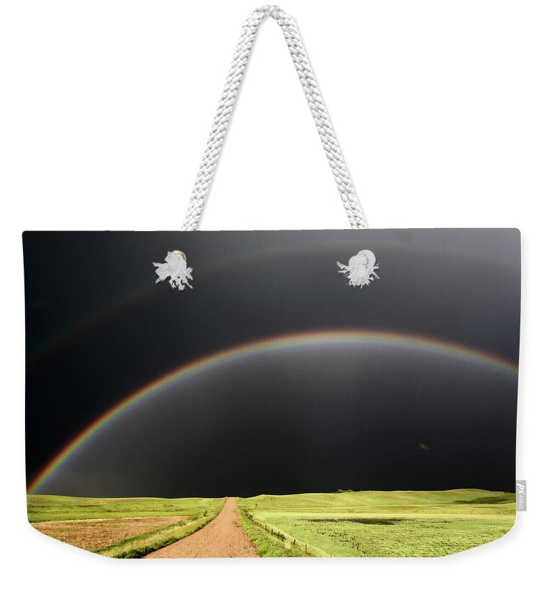 Rainbow Weekender Tote Bag featuring the digital art Rainbow And Darkened Skies Seen Down A Country Road by Mark Duffy