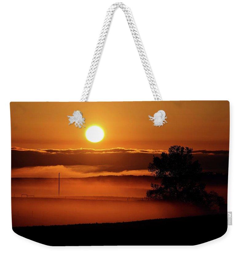 Weekender Tote Bag featuring the digital art Rising Sun Lighting Ground Fog by Mark Duffy