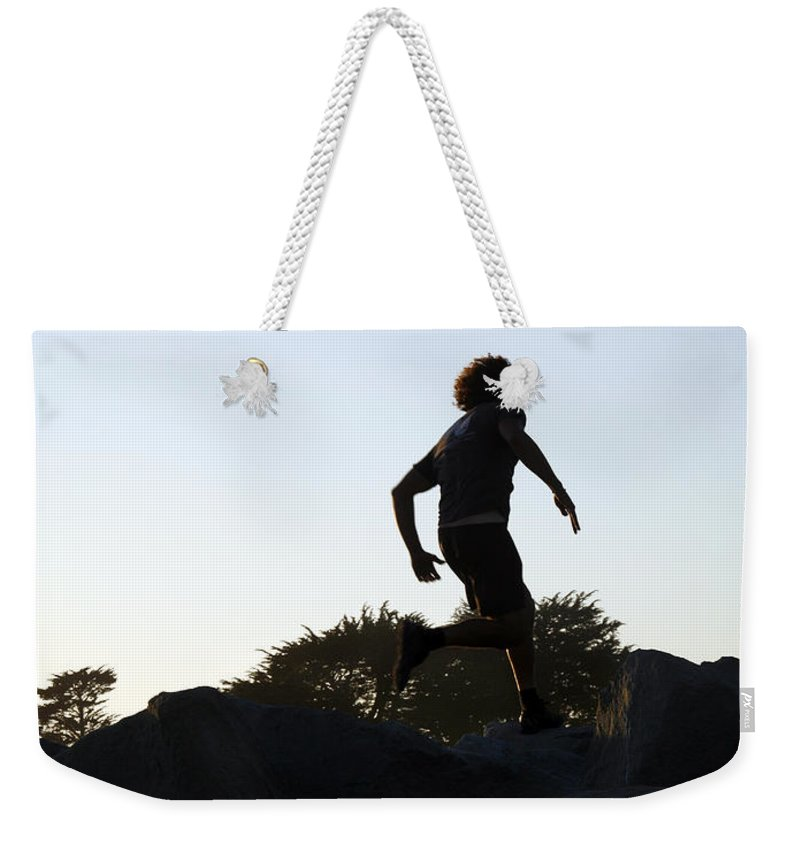Run Weekender Tote Bag featuring the photograph Runner by Marilyn Hunt