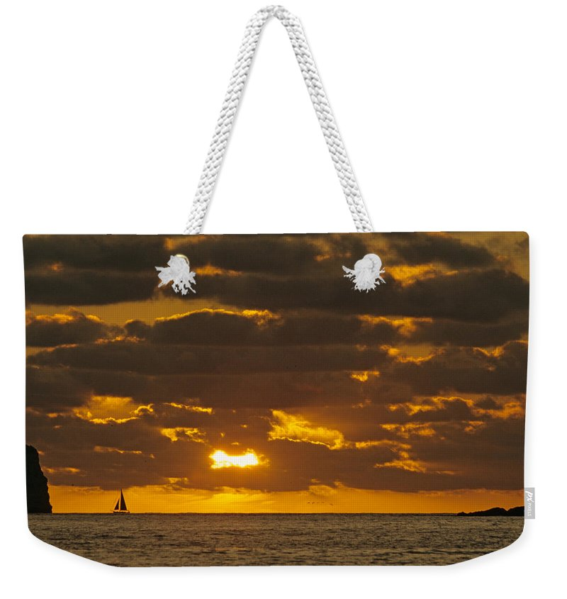 Sil Weekender Tote Bag featuring the photograph Sailboat As The Sun Sets by John Harmon