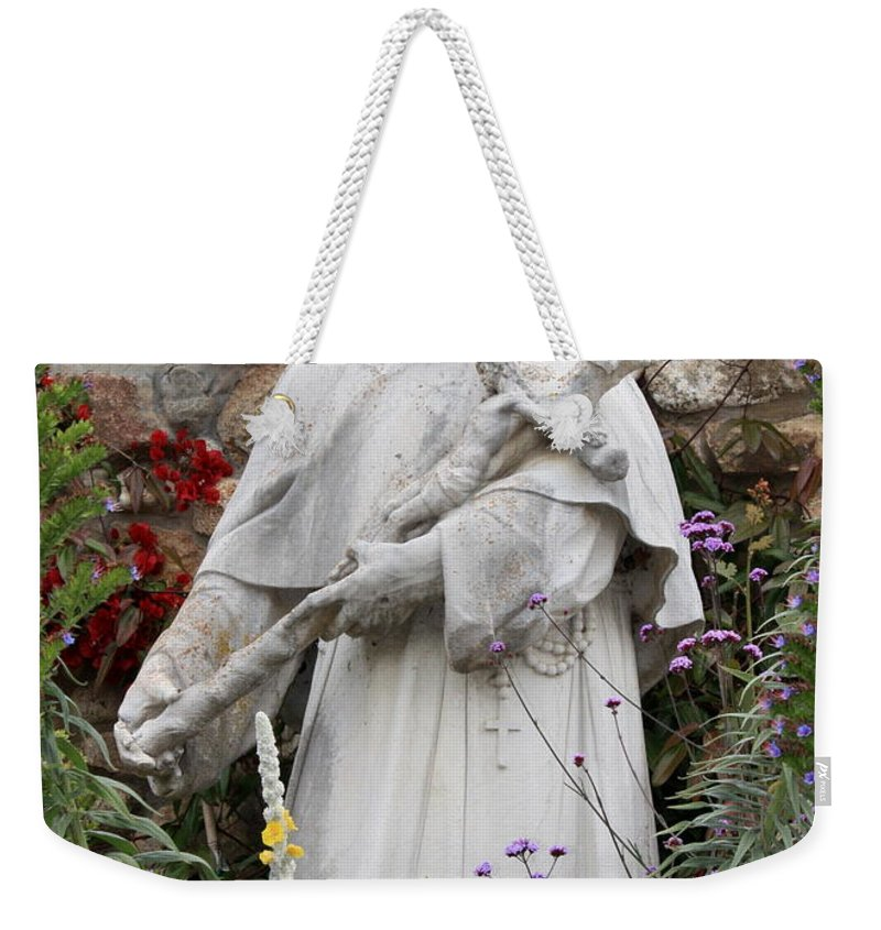 Saint Francis Weekender Tote Bag featuring the photograph Saint Francis Statue In Carmel Mission Garden by Carol Groenen