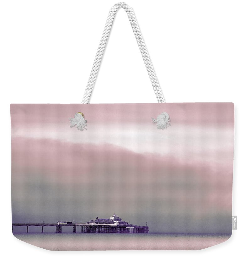 Pier Weekender Tote Bag featuring the photograph Sea Mist Replaces The Great Orme As The Backdrop To Llandudno Pier by Mal Bray
