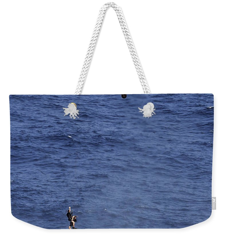 Navy Weekender Tote Bag featuring the photograph Search And Rescue Swimmers by Stocktrek Images