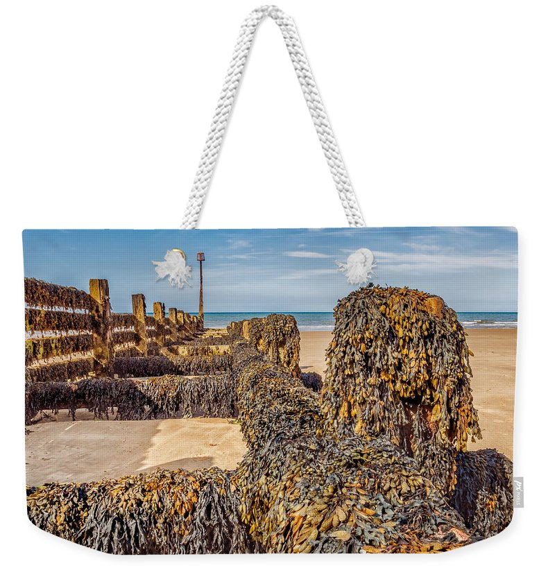 Sheringham Weekender Tote Bag featuring the photograph Seaweed Covered by Nick Bywater