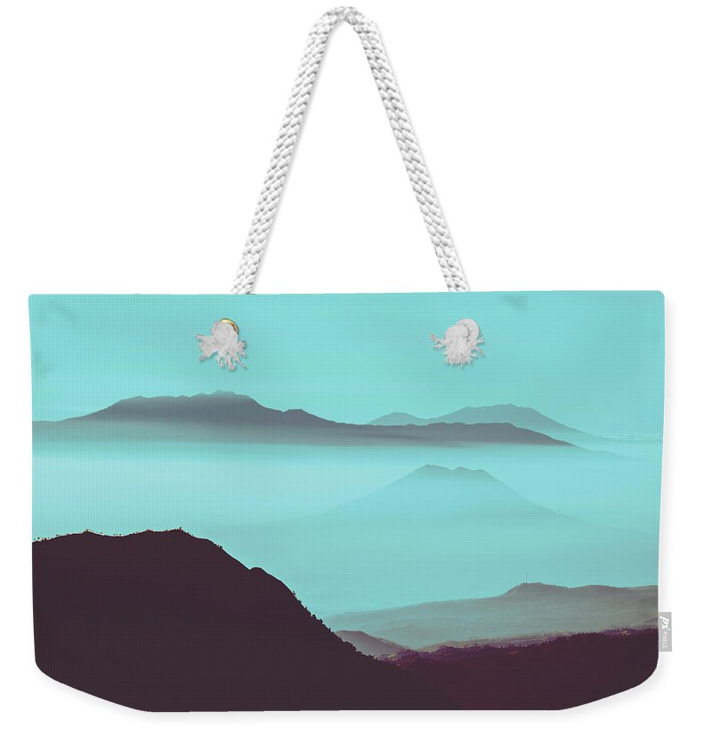 Adventure Weekender Tote Bag featuring the photograph Serene Scene Of A Early Morning Misty Clouds Rolling Over The Rugged Mountainous Terrain by Srdjan Kirtic