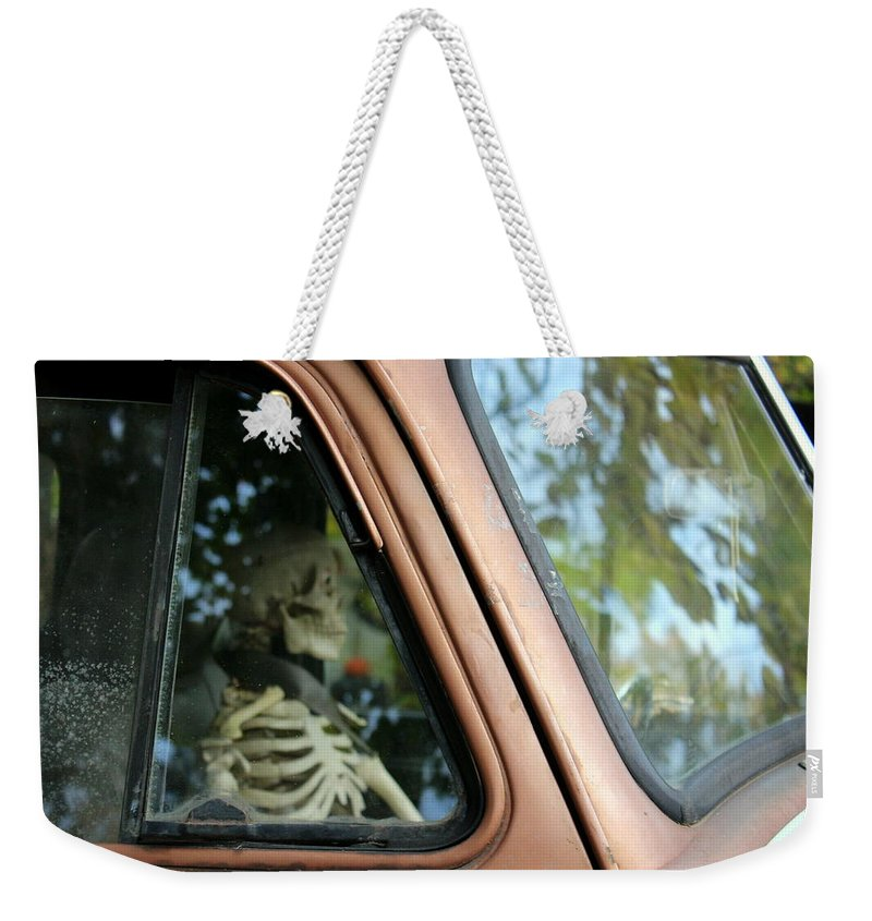 Skeleton Weekender Tote Bag featuring the photograph Skeleton Behind The Wheel Of Chevy Truck by Anita Hiltz